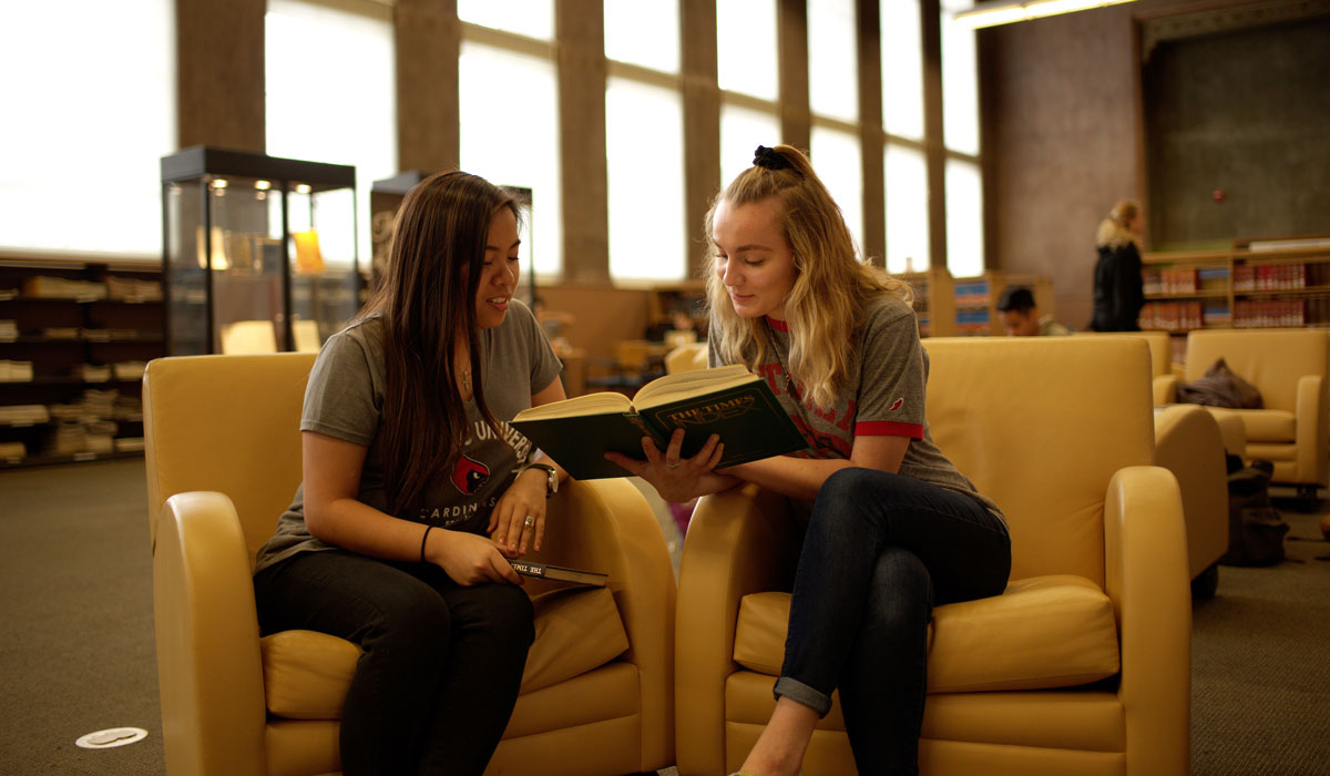 Two students sharing a book in the library
